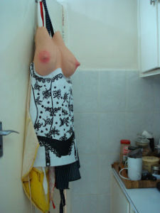 A joke cook's apron hangs from a peg. It has too large pink nippled rubber breasts protruding from the top.