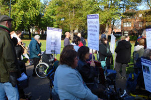 A large group of disabled people are gathered for a protest march. There are several banners and large signs, some people in wheelchairs, others standing. It is a bright sunny day.