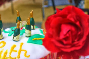 A red rose fills the right hand side of the frame and on the left, behind the rose, can be seen the top of a cake with small champagne bottle candles on white and green frosting.
