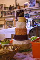 Cheese tower of different cheese rounds mounting from large to small, to celebrate the birthday of Ruth Hartley, mother, artist and author.