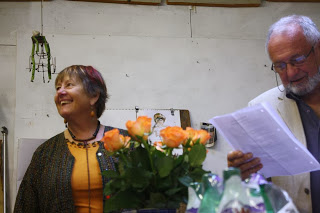Snapshot of Ruth Hartley in a yellow dress, laughing as she looks  to her right, while her partner John Corley reads or sings from a sheet he holds in front of him. They stand behind a vase of yellow-orange roses.