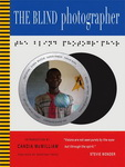 """Cover of """"The Blind Photographer"""" featuring images by Tanvir Bush and others, by Julian Rothenstein, introduced by Candia McWilliam and published by Redstone Press. The cover has three horizontal panels in blue, white and red, respectively, and a thin vertical column of yellow and black stripes at the leftmost edge. The white middle panel is the largest and contains a stylised image of a camera lens containing the image of a smiling black man. Above the lens is a text in braille."""