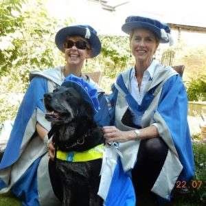 Guide dog Grace, a black labrador, wearing blue graduation cap and cape, sits proudly in front of similarly attired Dr. Tanvir Bush and another female graduate. All three are smiling!