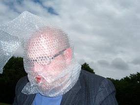 Head and shoulders shot of a bespectacled man in a dark jacket and a blue shirt with his head entirely covered in bubble wrap, except for his lips, which are visible through a hole in the wrap. Against a cloudy sky, he bends his head slightly forward. This image captures the claustrophobia, menace, and daftness of visual impairment experienced by Tanvir Bush as her retinitis pigmentosa advances.