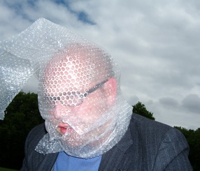 Head and shoulders shot of a bespectacled man in a dark jacket and a blue shirt with his head entirely covered in bubble wrap, except for his lips, which are visible through a hole in the wrap. Against a cloudy sky, he bends his head slightly forward.