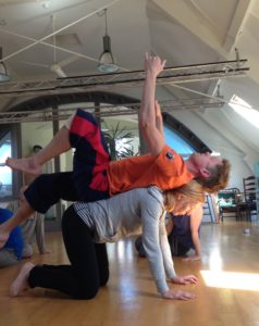 A slim woman in a long grey sleeved top and black legglings is on all fours in teh middle of a dance studio. A tall young man in orange T-shirt and jogging pants lies balanced on her back, facing the ceiling. His arms are raised and he is raising his legs.