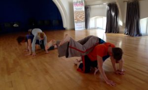 A sunny dance studio space. To the foreground a dancer in an orange t-shirt is on all fours whilst another dancer slies over their back. behind them another couple are doing the same exercise.