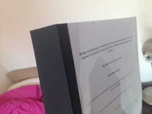 An very thick A4 sized thesis bound with black along the spine and with clear acetate over the title page.