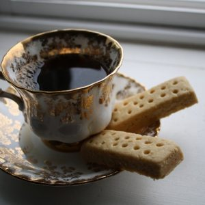 A beautiful and delicate cup and saucer are in the centre of the frame. the cup is full of dark coffee and there are two fingers of shortbread on the saucer.