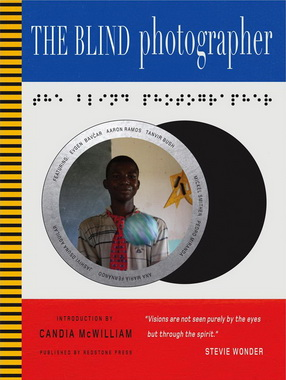 Cover of 'The Blind Photographer' featuting images by Tanvir Bush and others, introduced by Candia McWilliam and published by Redstone Press. The cover has three horizontal panels in blue, white and red, respectively, and a thin vertical column of yellow and black stripes at the leftmost edge. The white middle panel is the largest and contains a stylised image of a camera lens containing the image of a smiling black man. Above the lens is a text in braille.