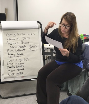 Tanvir Bush sits next to a flip-chart which lists the names of the participants, including that of her guide dog, Grace, in the Coming to our Senses workshop, February 2017, as she reads from a page held in her left hand, while she gesticulates with her right hand.