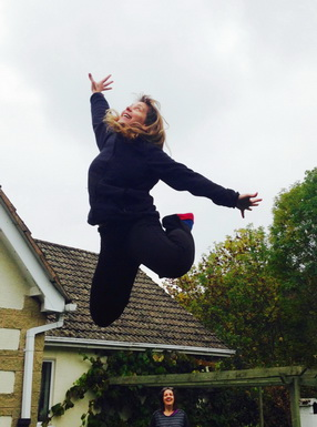 Dressed in a black jumper and black trousers, a grinning Tanvir Bush is seen mid-air, head thrown back, arms flung out, right arm stretched above her head, left arm stretched out to the side, with her knees bent and feet kicked up behind her. In the background is the brown-tiled roof of a house with the tops of two green trees. The head of a laughing woman enjoying the spectacle is visible in front of the house.