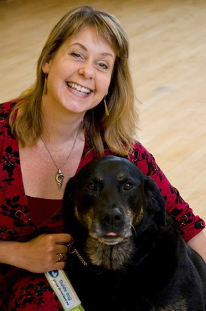 Dr. Tanvir Bush, wearing a scarlet dress with black detail, and a silver pendant in the shape of a shell, is smiling up at the camera as she crouches with her arm around her guide dog, black labrador Grace, who helps navigate her life despite her retinitis pigmentosa. Grace is looking straight at the camera.  Portrait by Penny Ellis