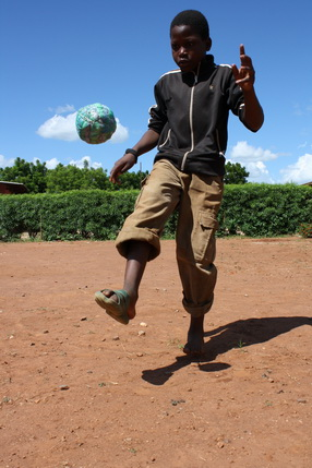 On a bright sunny day, a young black boy in a black tracksuit top and brown trowsers with rolled cuffs and sturdy flipflops is bouncing a football improvised from blue and green plastic bags and string. He is playing on a bare sandy pitch against a backdrop of blue African sky with a few white clouds and a green hedge.