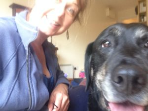 Slightly blurry selfie with middle aged woman in grey jacket grinning into the camera and closer is the smiling face, black with a little grey muzzle and brown eyes, of an older labrador/ retriever
