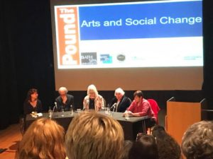 Five people sit behind a long table on a stage. The photo is taken from the audience and in the lower part of the frame are several heads partially blocking the view. The people sit facign the audience with 'The Arts and Soial Change' in a blue panel projected on the wall behind them. The far left of the panel is a woman with dark hair, a man with white hair and glasses is next to her, a slender woman, white-haired and with glasses next to him, an older woman shorter and with short white hair and then on the far right a woman with short dark hair and a red jumper leaning in.