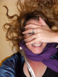 A woman is lying on her back, hair curling out around her head. She has a big grin on her face and her eyes are shut. She is covering her face with one hand.