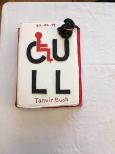 A very large cake with the CULL novel cover design on it in black and red with a 3d black dog in sugar fondant and a guide dog harness.