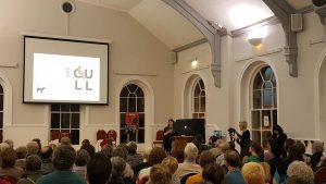 A view from the back of a large room with high ceilings and aerched windows. Lots of people are seated facing a large screen with CULL writtin on it and a woman behind a lectern facing and talking to the crowd.