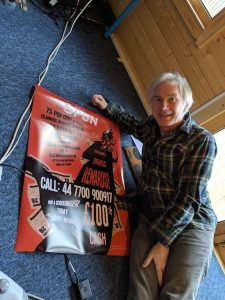 A man with blonde heair stands miling and holding an A2 size poster up against a wall. The poster ihas a red background and a strong black and white design on it with the words 'Shop a Scrounger' emblazoned.