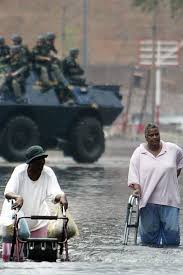 Rwo older black women are up to their waists in water, pushing wheeled zimmer frames with difficulty through the flood.