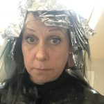 A woman looking directly and mornfully into the camera with her hair covered in foil as she is having her hair dyed.