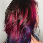 The back of a women's head with shoulder length hair in mutiple reds, pinks and blue colours.